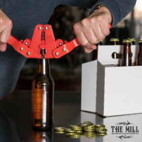 Homebrewer bottling beer with capper